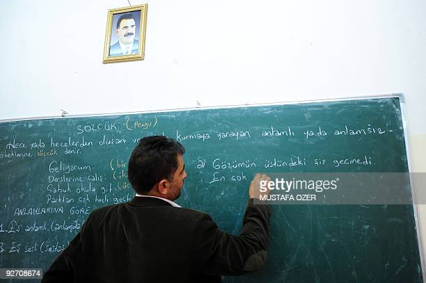 Kurdish refugee teacher writes on a blackboard during a Turkish class at a school at the Mahkmour refugees camp in Arbil northern Iraq on October 29...