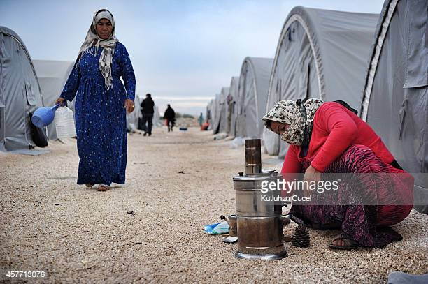 Kurdish refugee woman from the Syrian town of Kobani cook outside their family tent in a camp in the southeastern town of Suruc on October 23 2014 in...