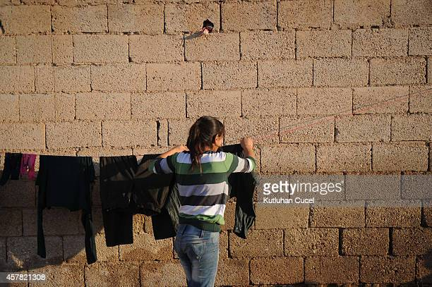 Kurdish refugee woman from the Syrian town of Kobani hangs out washing at their temporary shelter in a refugee camp in the southeastern town of Suruc...