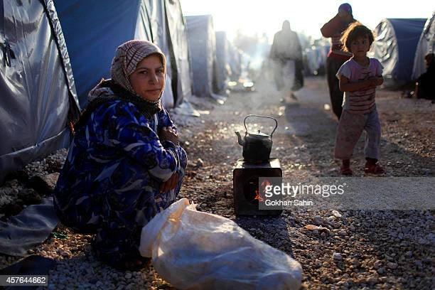 A Kurdish refugee woman from the Syrian town of Kobani prepares tea in front of her family tent in a camp in the southeastern town of Suruc Sanliurfa...