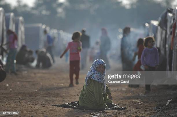 A Kurdish refugee woman sits on between the tents in a refugee camp on October 26 2014 in the southeastern town of Suruc Turkey The Syrian town of...