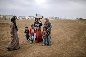Kurdish refugees are pictured during a rainy day in Suruc a rural district of Sanliurfa Province on October 30 2014 Heavily armed Kurdish peshmerga...