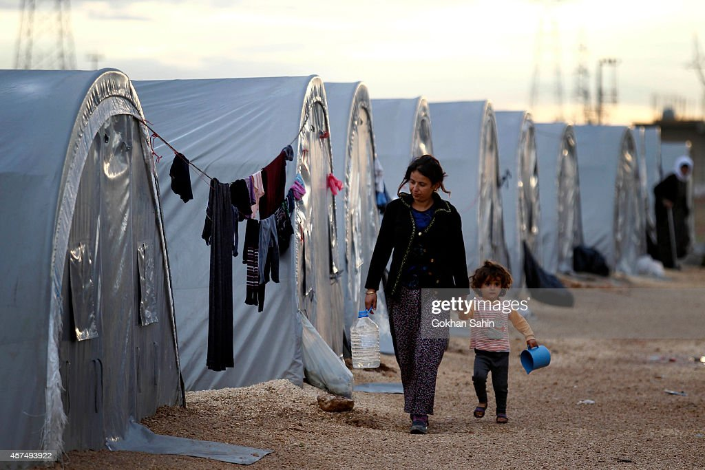 Kurdish refugees from the Syrian town of Kobani walk besides their tents in a camp in the southeastern town of Suruc on the TurkishSyrian border...
