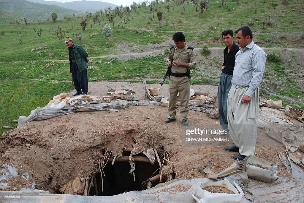 Kurdish security officers look at the shell damage to a roof following an Iran attack on Narmalas 165 kms from the northern city of Sulaimaniyah...