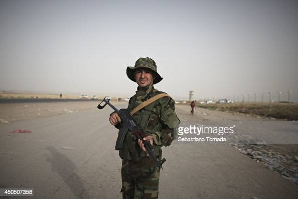 A kurdish soldier at one of the checkpoints that have been recently opened to refugees fleeing from Iraq after ISIS militants have overrun and taken...