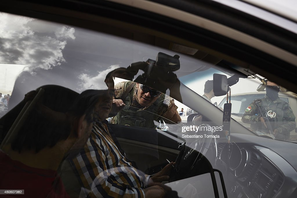 A Kurdish soldier interrogates a family of Iraqis fleeing violence after ISIS overrun the city of Mosul. June 12, 2014.