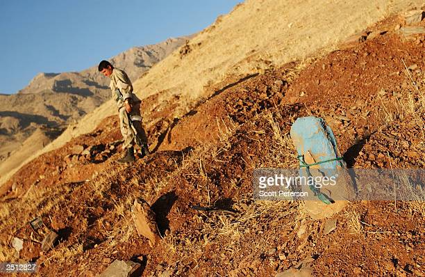 Kurdish soldier of the Patriotic Union of Kurdistan walks past an Ansar grave during a survey September 9 2003 of the wreckage of the military base...