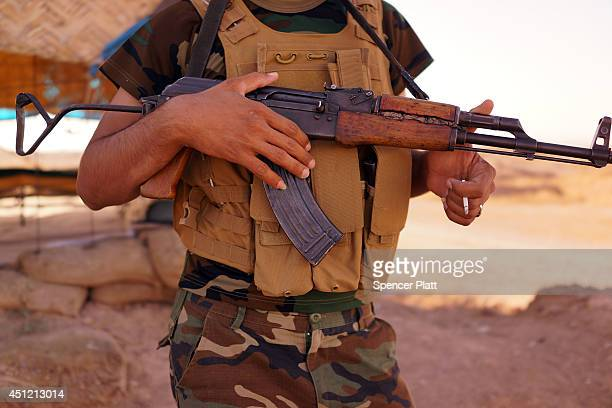 Kurdish soldier with the Peshmerga keeps guard near the frontline with Sunni militants on the outskirts of Kirkuk an oilrich Iraqi city on June 25...