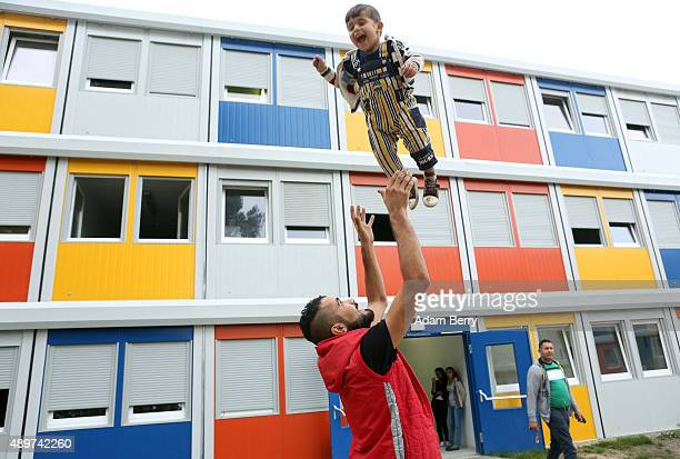 Kurdish Syrian migrant plays with 3yearold Kurish Syrian child refugee Ivan at a temporary shelter for migrants constructed from shipping containers...