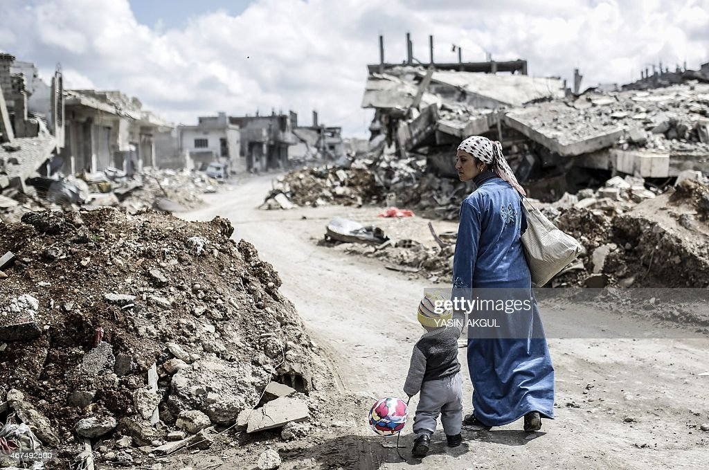 A Kurdish Syrian woman walks with her child past the ruins of the town of Kobane also known as Ain alArab on March 25 2015 Islamic State fighters...