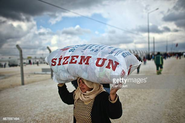 Kurdish woman carries a sack of clothes on her head as she walks through Suruc refugee camp on March 25 2015 in Suruc Turkey The camp is the largest...