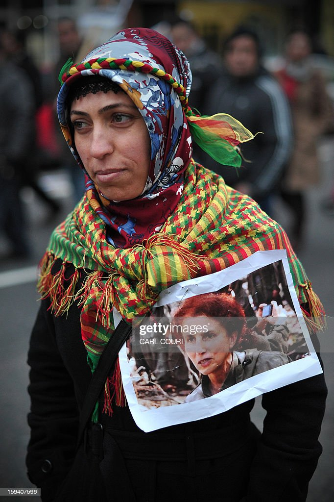 A Kurdish woman displays a picture of Sakine Cansiz, one of three top Kurdish activists from a separatist group banned in Turkey who were killed earlier this week in France, during a rally demanding them justice in north London on January 13, 2013. The three activists -- Sakine Cansiz, Fidan Dogan and Leyla Soylemez -- were found dead on January 10 at the Kurdistan Information Centre in the grimy 10th district of Paris, after last being seen alive at the centre at midday on January 9.