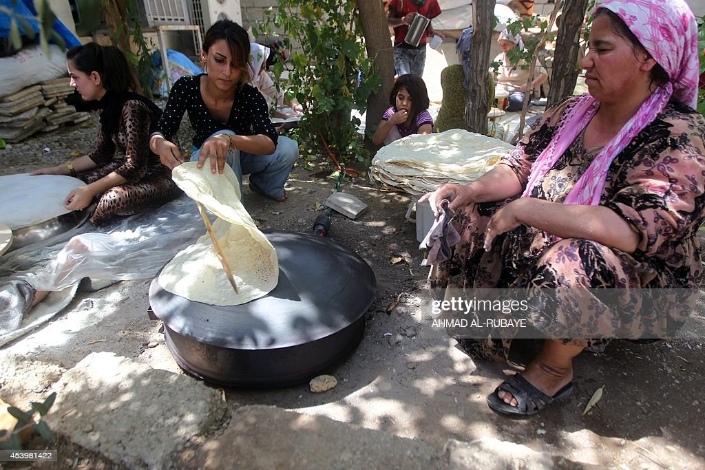 Kurdish women bake bread on a typical domed metal griddle for baking traditional flat bread, known locally in the region as the saj, at the mosque where they sought refuge in the village of Hajyawa in Iraq's Sulaimaniyah district on August 21, 2014, after fleeing their first place of refuge in Makhmur following an offensive by Islamic State (IS) militants. Families who once fled a massive Turkish crackdown on Kurdish rebels in the 1990s now rest in a northern Iraq mosque after escaping brutal jihadists, longing to return home.