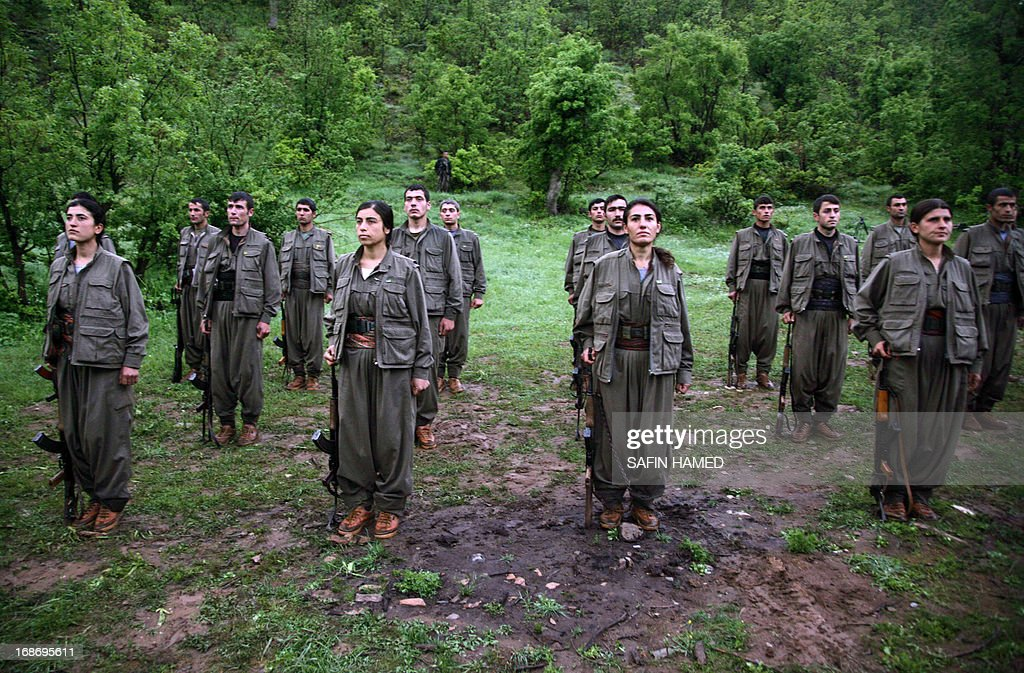 Kurdistan Workers' Party (PKK) stand to attention after arriving in the northern Iraqi city of Dohuk on May 14, 2013, after leaving Turkey as part of a peace drive with Ankara. The PKK has fought a 29-year nationalist campaign against Ankara in which some 45,000 people have died, but is now withdrawing its fighters from Turkey as part of a push for peace with the Turkish authorities.