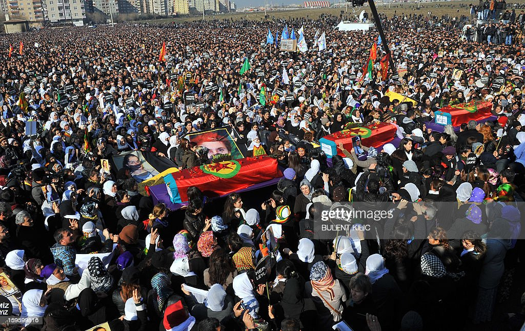 Kurds carry the coffins of the three top Kurdish activists Sakine Cansiz, Fidan Dogan and Leyla Soylemez, shot dead in the French capital, on January 17 in Diyarbakir. Several thousand Kurds gathered Thursday in a square in Diyarbakir, the main city of Turkey's Kurd-majority southeast, to pay a final tribute to three Kurdish women activists who were assassinated in Paris last week. The growing crowd of participants, men and women adorned in white scarves, a symbol of peace, marched in a funeral many in Turkey feared would turn into a violent protest. The three women, one of them Sakine Cansiz, a co-founder of the outlawed Kurdistan Workers' Party (PKK), were found fatally shot, at least three times in their heads, at a Kurdish centre in Paris last week. French police were hunting the unknown assailants. AFP PHOTO/BULENT KILIC