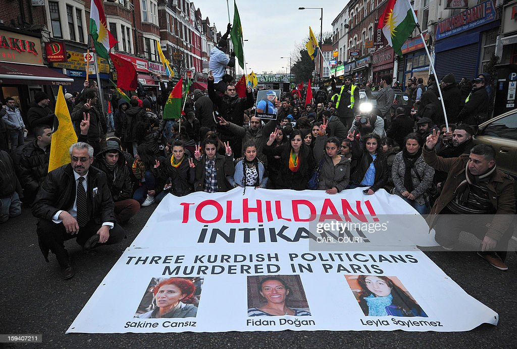 Kurds hold a banner bearing pictures of three top Kurdish activists from a separatist group who were killed earlier this week in France during a rally in north London on January 13, 2013. The three activists -- Sakine Cansiz, Fidan Dogan and Leyla Soylemez -- were found dead on January 10 at the Kurdistan Information Centre in the grimy 10th district of Paris, after last being seen alive at the centre at midday on January 9.