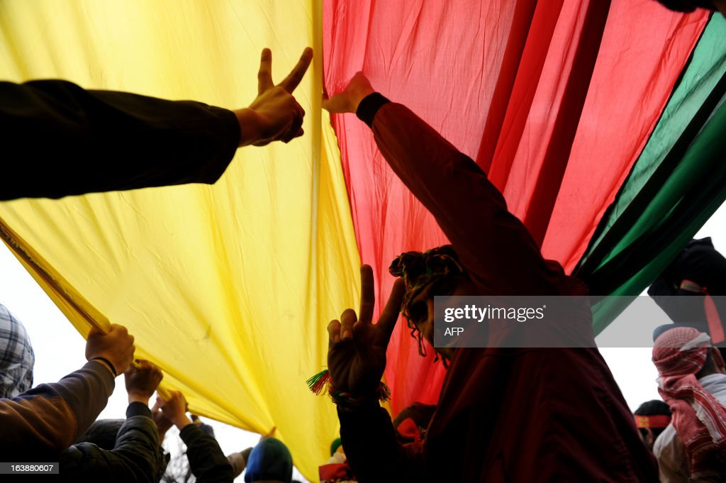 Kurds hold a giant flag of PKK (Kurdish Workers Party) and flash V-signs during celebrations on March 17, 2013 of Nowruz, the Persian New Year festival, in Kazlicesme, Istanbul. The festival is celebrated in Turkey, Central Asian republics, Iraq, Iran, Azerbaijan as well as war-torn Afghanistan and coincides with the astronomical vernal equinox., in kazlicesme istanbul. The festival is celebrated in Turkey, Central Asian republics, Iraq, Iran, Azerbaijan as well as war-torn Afghanistan and coincides with the astronomical vernal equinox. AFP PHOTO/OZAN KOSE