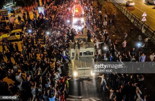 Kurds in Turkey greet peshmerga convoys at Viransehir in Sanliurfa on October 29 2014 Heavily armed Kurdish peshmerga fighters were on their way by...