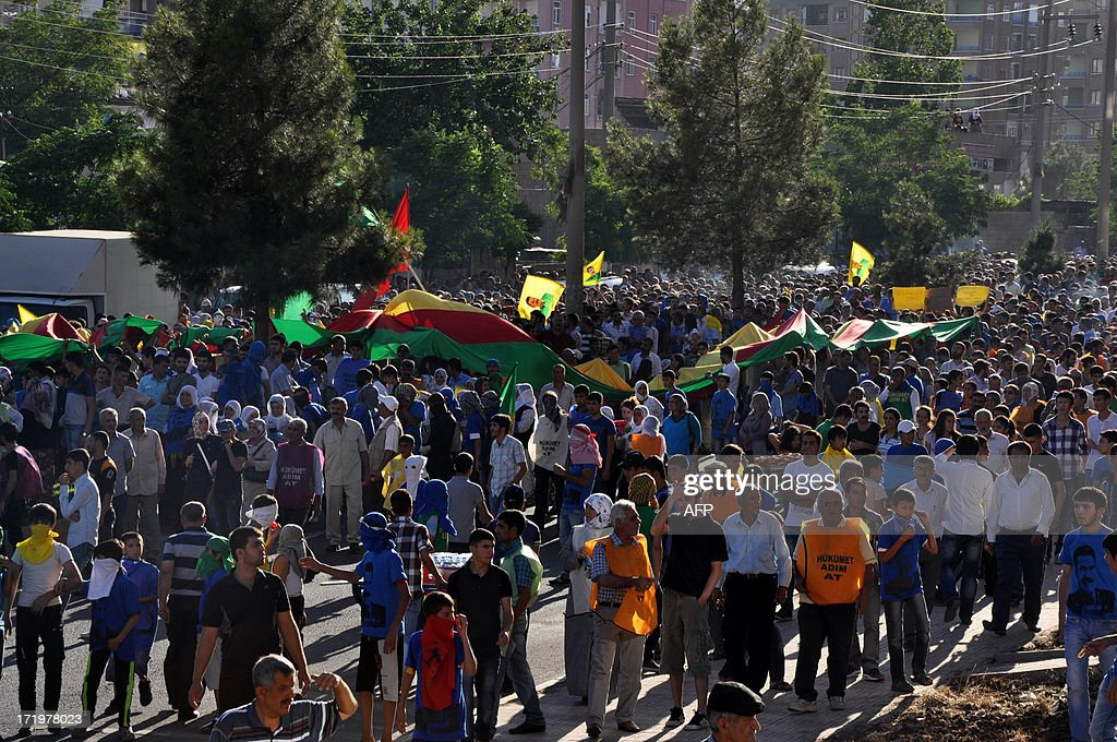 Kurds march with a giant Kurdish flag during a protest on June 30, 2013, in Diyarbakir. Turkish security forces killed one person and wounded seven on June 28 when they fired on a group of people protesting against the construction of a new gendarmerie outpost in the Kurdish-dominated southeastern Turkey, security sources said. AFP PHOTO/MEHMET ENGIN