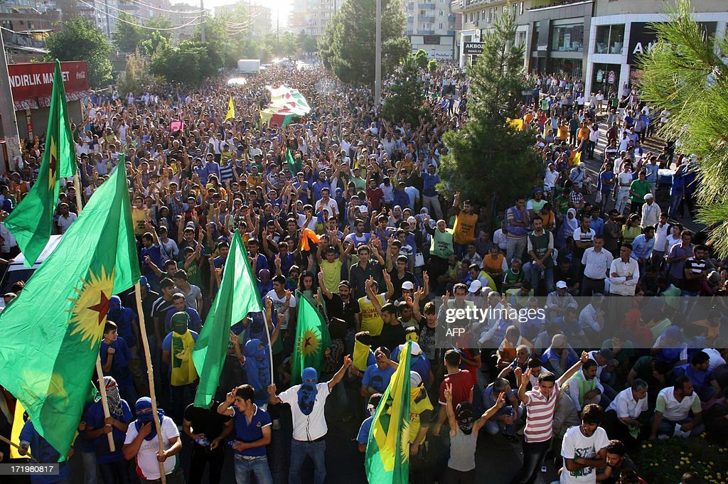 Kurds march with a giant Kurdish flag during a protest on June 30, 2013 in Diyarbakir. Turkish security forces killed one person and wounded seven on June 28 when they fired on a group of people protesting against the construction of a new gendarmerie outpost in the Kurdish-dominated southeastern Turkey, security sources said. AFP PHOTO/MEHMET ENGIN