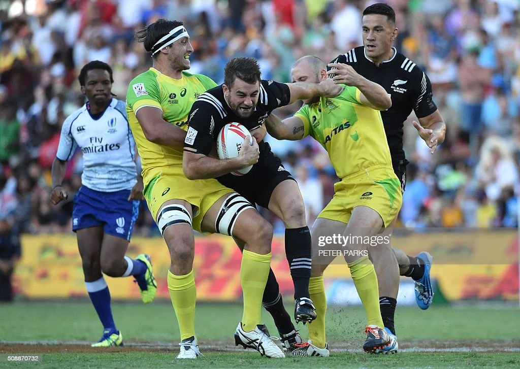 Kurt Baker of New Zealand (C) is tackled by James Stannard (2nd-R) and Lewis Holland of Australia (L) as his teammate Sonny Bill Williams (R) looks on in the Cup final in the Sydney Sevens rugby union tournament in Sydney on February 7, 2016. AFP PHOTO / Peter PARKS -- IMAGE