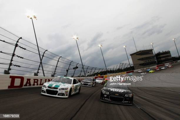 Kurt Busch driver of the Furniture Row Racing / Serta Chevrolet and Jimmie Johnson driver of the Lowe's Emerald Green Chevrolet lead the field before...