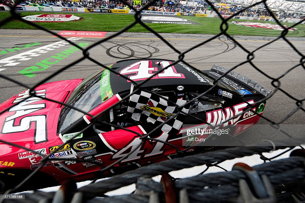 Kurt Busch driver of the Haas Automation Chevrolet celebrates with the checkered flag after winning the NASCAR Sprint Cup Series Toyota Owners 400 at...