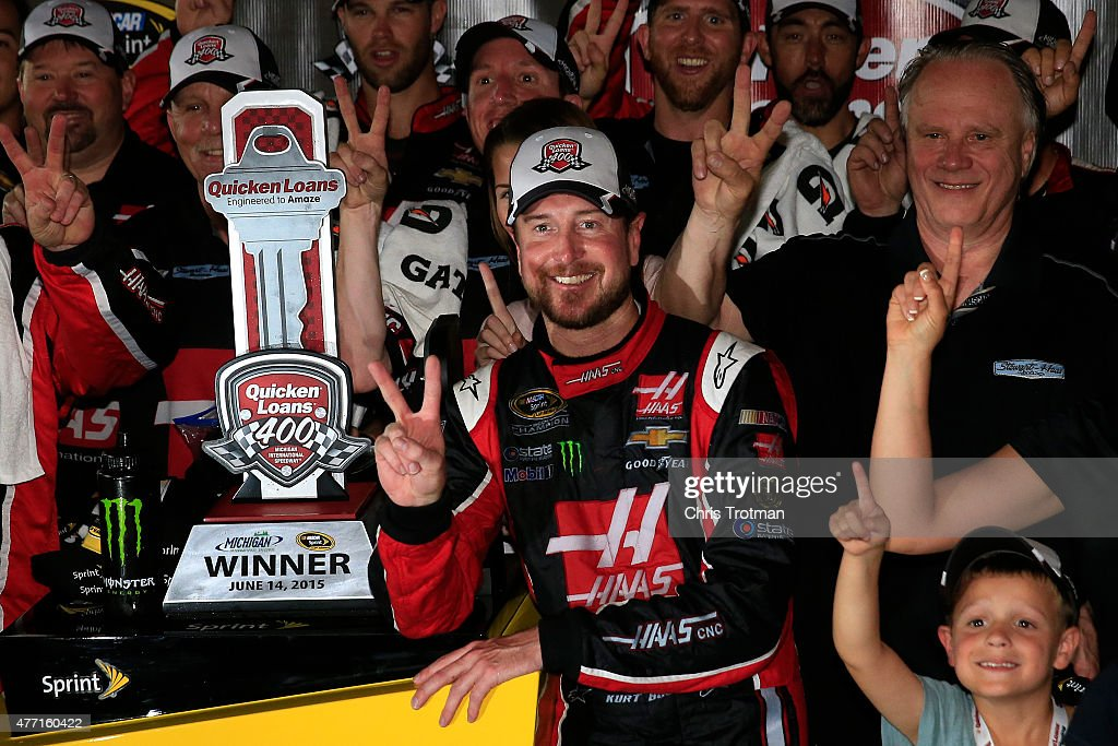 Kurt Busch, driver of the #41 Haas Automation Chevrolet, Gene Haas, co-owner of Stewart Haas Racing, and his team pose in an alternate Victory Lane after winning the NASCAR Sprint Cup Series Quicken Loans 400 at Michigan International Speedway on June 14, 2015 in Brooklyn, Michigan.