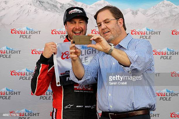 Kurt Busch driver of the Haas Automation Chevrolet left and Texas Motor Speedway President Eddie Gossage pose for a selfie after Busch qualified for...