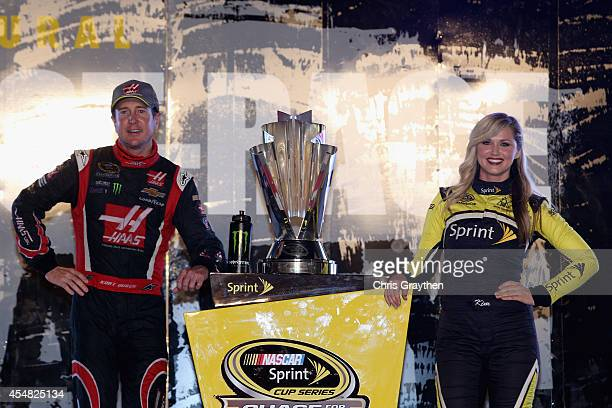 Kurt Busch driver of the Haas Automation Chevrolet poses with the Sprint Cup Trophy and Miss Sprint Cup Kim Coon after qualifying for the Chase for...