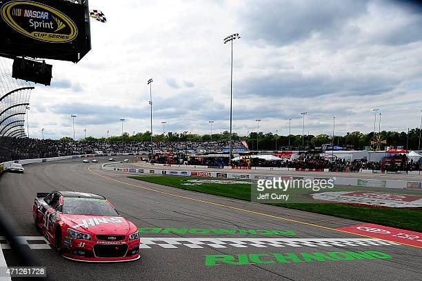 Kurt Busch driver of the Haas Automation Chevrolet takes the checkered flag to win the NASCAR Sprint Cup Series Toyota Owners 400 at Richmond...