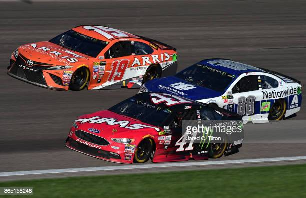 Kurt Busch driver of the Haas Automation/Monster Energy Ford leads Daniel Suarez driver of the ARRIS Toyota and Dale Earnhardt Jr driver of the...