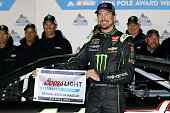 Kurt Busch driver of the Monster Energy/Haas Automation Chevrolet poses with the Coors Light Pole Award after qualifying for pole position for the...