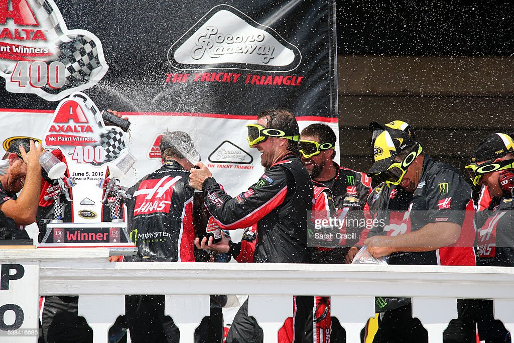 Kurt Busch driver of the Monster Energy/Haas Automation Chevrolet celebrates with his team in Victory Lane after winning the NASCAR Sprint Cup Series...