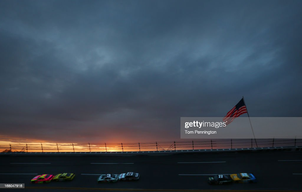 Kurt Busch driver of the Phoenix Construction Chevrolet leads cars down the backstretch as the sun sets during the NASCAR Nationwide Series Aaron's...