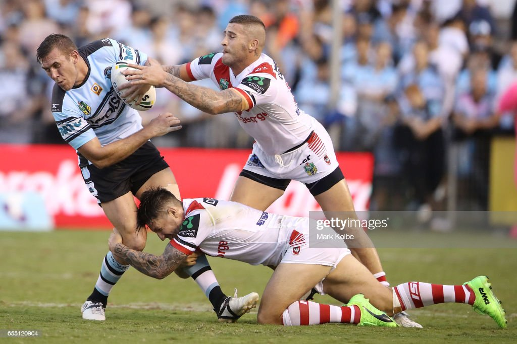 Kurt Capewell of the Sharks is tackled by Gareth Widdop and Joel Thompson of the Dragons during the round three NRL match between the Cronulla Sharks and the St George Illawarra Dragons at Southern Cross Group Stadium on March 19, 2017 in Sydney, Australia.