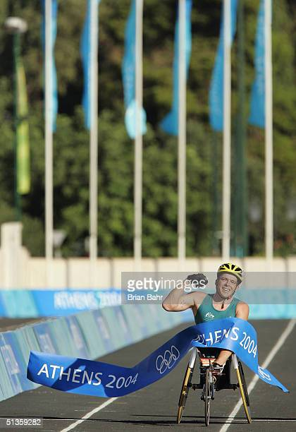 Kurt Fearnley of Australia pulls down the tape as the first across the finish line in the Mens Marathon on September 26 2004 during the 2004...