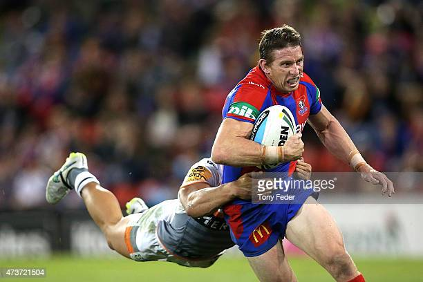 Kurt Gidley of the Knights is tackled by the Tigers defence during the round 10 NRL match between the Newcastle Knights and the Wests Tigers at...