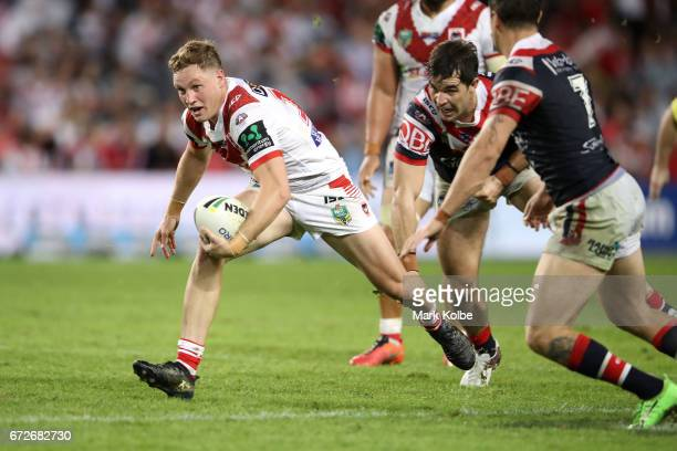 Kurt Mann of the Dragons tores to evade the tackle of Aidan Guerra and Mitchell Pearce of the Roosters during the round eight NRL match between the...