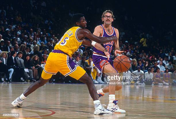 Kurt Rambis the Phoenix Suns pass the ball by AC Green of the Los Angeles Lakers during an NBA basketball game circa 1991 at The Forum in Los Angeles...