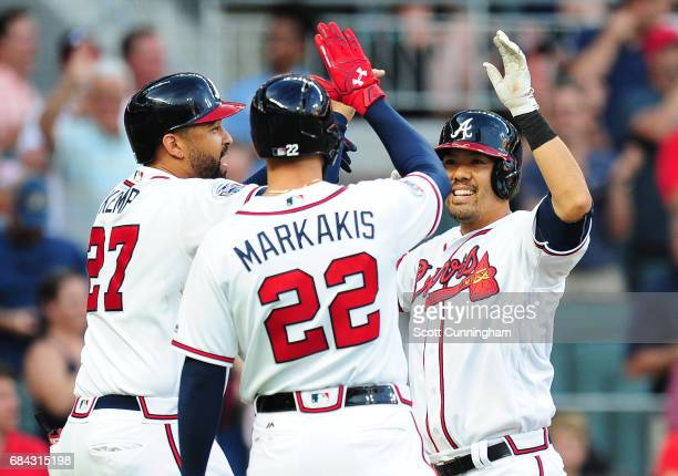 Kurt Suzuki of the Atlanta Braves is congratulated by Matt Kemp and Nick Markakis after hitting a first inning threerun home run against the Toronto...