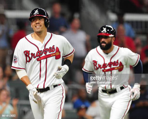 Kurt Suzuki of the Atlanta Braves leads Nick Markakis back to the dugout after hitting a two run home run in the first inning against the...
