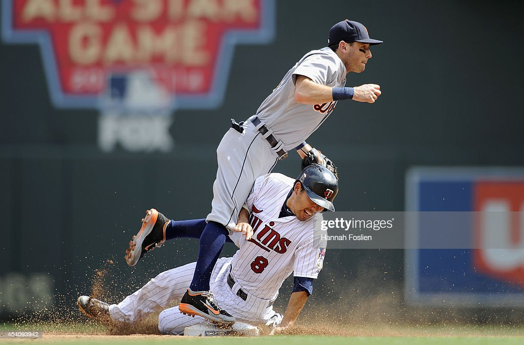 Kurt Suzuki of the Minnesota Twins breaks up a double play attempt by Ian Kinsler of the Detroit Tigers during the third inning of the game on August...