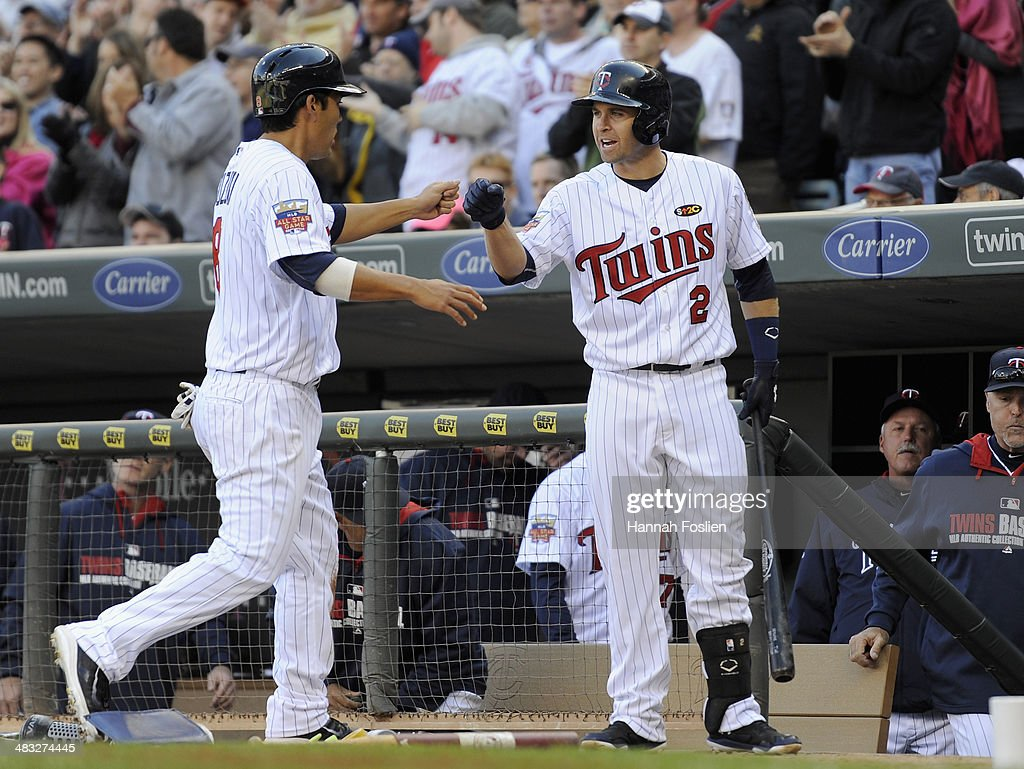 <a gi-track='captionPersonalityLinkClicked' href=/galleries/search?phrase=Kurt+Suzuki&family=editorial&specificpeople=682702 ng-click='$event.stopPropagation()'>Kurt Suzuki</a> #8 of the Minnesota Twins celebrates scoring a run with teammate <a gi-track='captionPersonalityLinkClicked' href=/galleries/search?phrase=Brian+Dozier&family=editorial&specificpeople=7553002 ng-click='$event.stopPropagation()'>Brian Dozier</a> #2 against eh Oakland Athletics during the second inning of the home opening game on April 7, 2014 at Target Field in Minneapolis, Minnesota.
