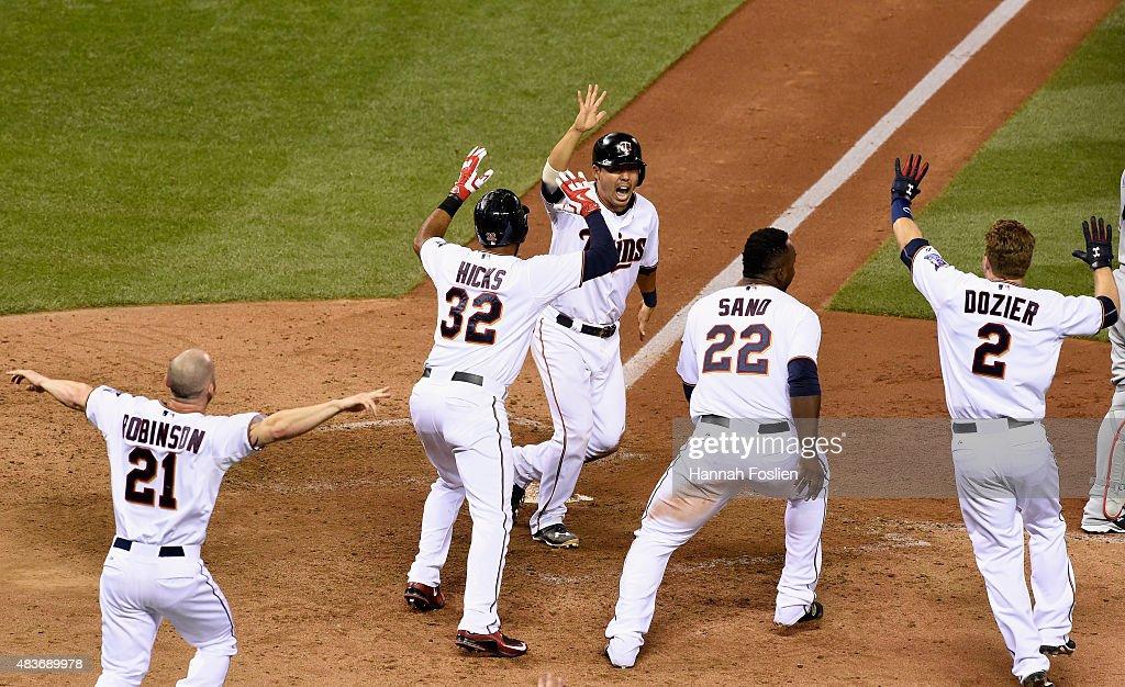 Kurt Suzuki of the Minnesota Twins celebrates sliding across home plate against the Texas Rangers during the ninth inning as teammates Shane Robinson...