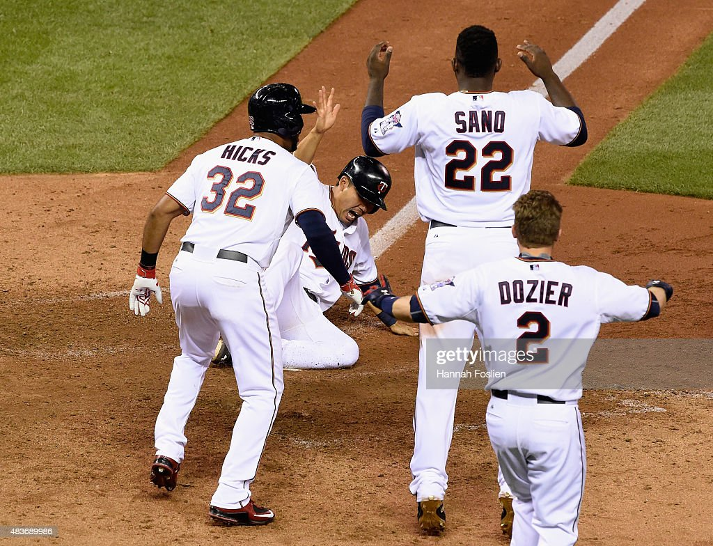 Kurt Suzuki of the Minnesota Twins celebrates sliding across home plate against the Texas Rangers during the ninth inning as teammate Aaron Hicks...