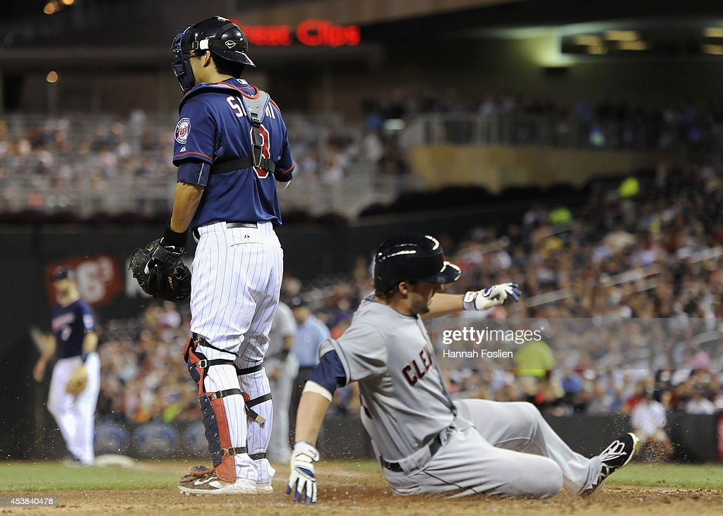 <a gi-track='captionPersonalityLinkClicked' href=/galleries/search?phrase=Kurt+Suzuki&family=editorial&specificpeople=682702 ng-click='$event.stopPropagation()'>Kurt Suzuki</a> #8 of the Minnesota Twins looks on as Tyler Holt #62 of the Cleveland Indians slides safely into home plate during the sixth inning of the game on August 19, 2014 at Target Field in Minneapolis, Minnesota. The Indians defeated the Twins 7-5.