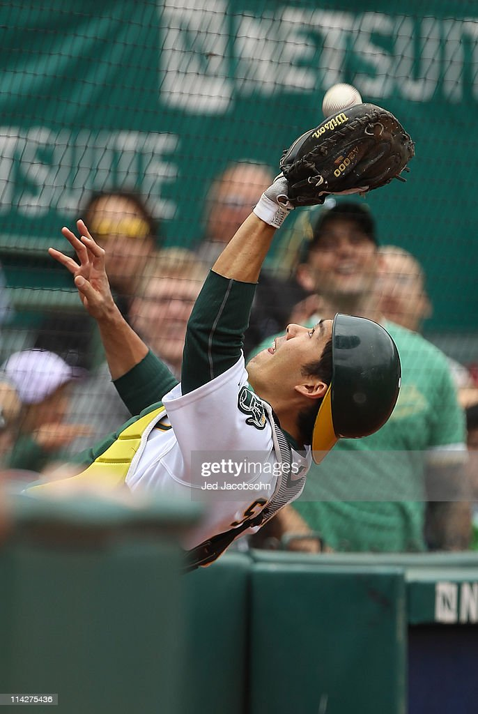 <a gi-track='captionPersonalityLinkClicked' href=/galleries/search?phrase=Kurt+Suzuki&family=editorial&specificpeople=682702 ng-click='$event.stopPropagation()'>Kurt Suzuki</a> #8 of the Oakland Athletics catches a foul ball against the Chicago White Sox during a Major League Baseball game at the Oakland-Alameda County Coliseum on May 14, 2011 in Oakland, California.