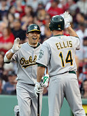 Kurt Suzuki of the Oakland Athletics celebrates with teammate Mark Ellis after Suzuki hit a two run homer in the first inning off a pitch from...