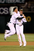 Kurt Suzuki of the Oakland Athletics congratulates Mark Ellis after Ellis got the gamewinning hit in the tenth inning against the Seattle Mariners at...